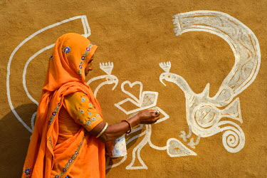 HMS1992644 India, Rajasthan, Tonk region, Woman painting clay walls prior to Diwali festival. These paintings are meant to welcome goddess Lakshmi and ward off evil spirits