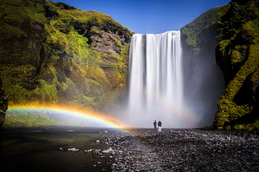 ICE3531AW Iceland, Skogafoss waterfall with double rainbow and tourists admiring the natural wonder