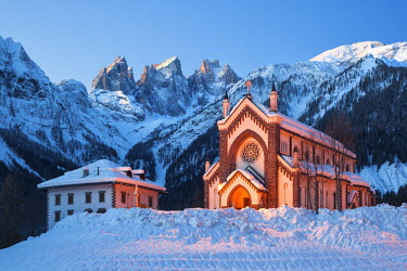 CLKMG9882 The church of Falcade, with Focobon peaks in the background, in wintertime, Dolomites, Belluno, Italy