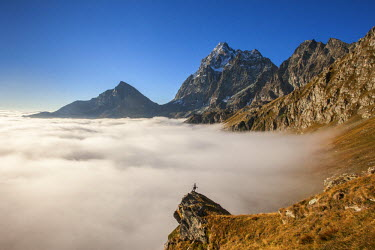 CLKRG6006 A cloud's sea, in autumn, under Monviso peak and Viso Mozzo peak, with an alpinist on a pulpit rock. Piedmont, Italy