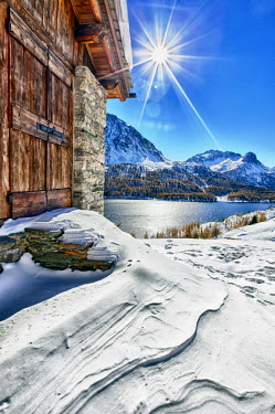 CLKRM4883 The sun is reflected in the Lake of Sils after an autumn snowfall from one of the huts in Spluga. Engadine. Switzerland. Europe