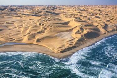 CLKRM5304 Aerial shot of the cold waters of the Atlantic Ocean meeting the sand dunes of the Namib Desert. Namibia. Africa