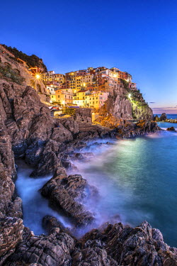 CLKRM6178 Manarola village illuminated by the blue light of dusk with its typical pastel colored houses. Cinque Terre National Park. La Spezia. Liguria. Italy. Europe