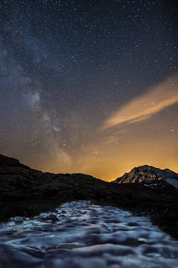 CLKRM13768 The Milky Way shining over Mount Disgrazia while a stream is quietly flowing towards the valley. Valmalenco. Valtellina. Lombardy. Italy