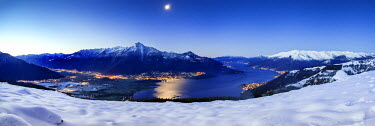 CLKRM13889 Wide angle shot of Alto Lario with Como lake and mount Legnone lighted by the moon in winter. Lombardy. Italy