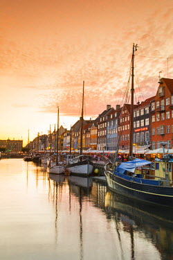 DEN0173AW Denmark, Hovedstaden, Copenhagen. Colourful buildings along the 17th century waterfront of Nyhavn at sunset.