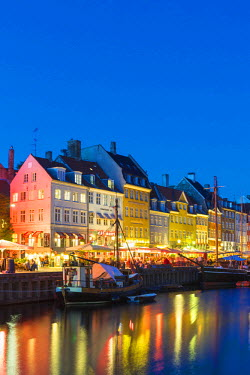 DEN0183AW Denmark, Hovedstaden, Copenhagen. Colourful buildings along the 17th century waterfront of Nyhavn at dusk.