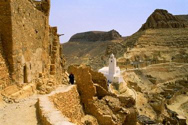 TUN1091AW Priest walking along a path in Chenini, Tunisia, Africa
