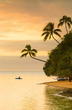 FIJ1050AW Woman kayaking at sunset, Leleuvia Island, Lomaiviti Islands, Fiji