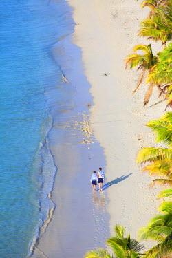 FIJ1060AW Boys walking on beach at Mana Island Resort, Mana Island, Mamanuca Islands, Fiji