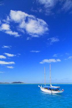 FIJ1145AW Yacht in lagoon with Malolo Island, Mamanuca Islands, Fiji