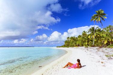 CKI0047AW Tourist lying on sand, on a small island in Aitutaki lagoon, Cook Islands (MR)