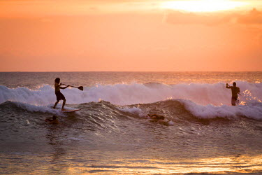 CR33153AW Costa Rica, Playa Santa Teresa, Mal Pais. Surfers and paddleboarding surf at the Pacific Ocean, sunset.