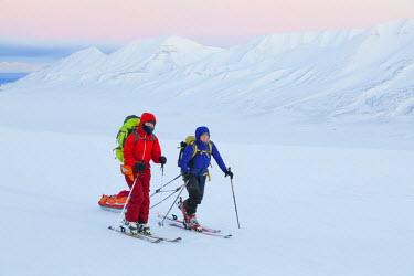 ARWEET001316 Young women ski across Breinosa, Svalbard