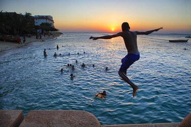 ARGADA000427 A boy jumps in the sea, Zanzibar Town, Zanzibar, Tanzania.
