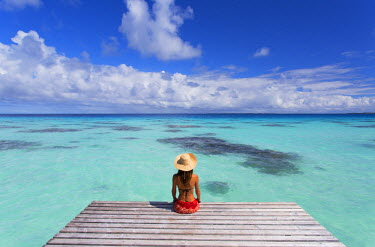 FPO0371AW Woman sitting on jetty, Fakarava, Tuamotu Islands, French Polynesia (MR)