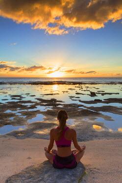 FPO0418AW Woman practicing yoga on beach at sunrise, Fakarava, Tuamotu Islands, French Polynesia (MR)
