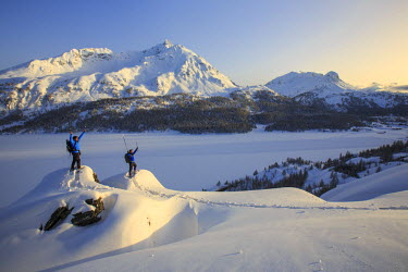 CLKRM18425 Snowshoe hikers, Lake Sils and the snow covered Piz de la Margna. Maloja Pass. Engadine. Switzerland. Europe
