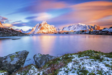 CLKRM24554 The pink sky at sunrise illuminates Reine village with its cold sea and the snowy peaks. Lofoten Islands Northern Norway Europe
