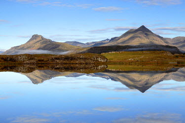 ICE3538 Mountains of Iceland's East Fjords reflected in calm water near Djupivogur