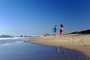 AUS2081 Teenage boy and girl run along Sunshine Beach, Noosa, Queensland, Australia (MR)