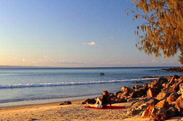 AUS2097 A teenage girl sits on a sunny beach beneath a casuarina tree at Noosa on the Sunshine Coast, Queensland, Australia, with surfers in the background (MR)