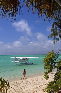 AUS2119 A young woman walks along the coral sand beach of Heron Island on the Great Barrier Reef, a floatplane moored in the tropical lagoon, Queensland, Australia (MR)