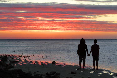 AUS2121 A mother and sun watch the sunset from Heron Island on the Great Barrier Reef, Queensland, Australia (MR)