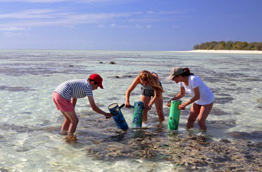 AUS2124 A family use underwater vievers during a reef walk at low tide across the lagoon, or reef flat, of Heron Island on the Great Barrier reef, Queensland, Australia