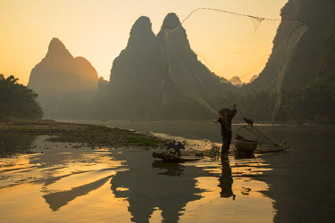 CH10530AW Cormorant fisherman throwing net on Li River at dawn, Xingping, Yangshuo, Guangxi, China