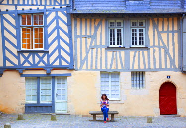 France, Brittany, Rennes. Young woman sitting in front of a typical facade found in the historic centre. MR