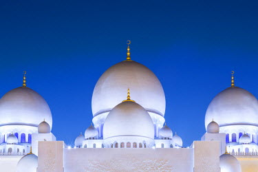 UAE0358AW United Arab Emirates, Abu Dhabi. The white marble domes of Sheikh Zayed Grand Mosque. The main dome pictured is 85m high and comparable in size to St Paul's Cathedral. The spectacular evening lighting...