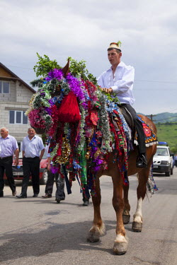 ROM1318 Romania, Maramures, Sieu. A young man in traditional Maramures dress astride a heavily decorated horse taking part in a procession.