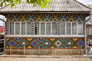 ROM1329 Romania, Maramures, Sarbi. A house covered in colourful tiles, a traditional Maramures style of decoration.