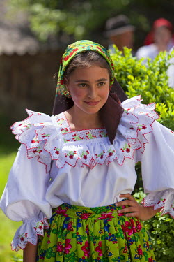 ROM1385 Romania, Maramures, Rozavlea. Young girl in traditional Maramures dress attending a blessing and ceremony in remembrance of war heroes.