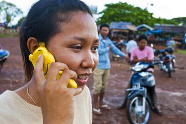 HMS0533568 Cambodia, Kompong Chhnang Province, Kampong Lang village along the Tonle Sap, a villager with mobile phones