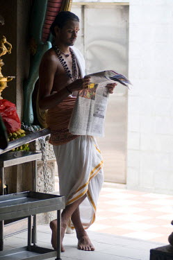 HMS1855318 Singapore, Litle india, temple Sri Veeramakaliamman dedicated to Shiva, young priest reading a newspaper