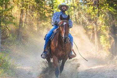 CA01190 Cowboy galloping through woods, British Columbia, Canada