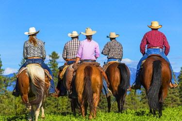 CA01191 Cowboys & cowgirls galloping horses across grassland British Columbia, Canada