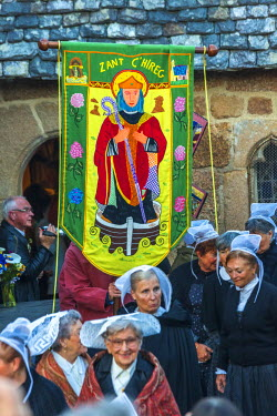 FR05590 Breton ladies outside church in traditional dress for ceremony of Saint Guirec, Ploumanach, Cote de Granit Rose, Cotes d'Amor, Brittany, France