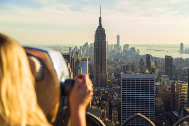 US61180 Woman looking through coin operated telescope over Empire State Building & Manhattan, New York, USA