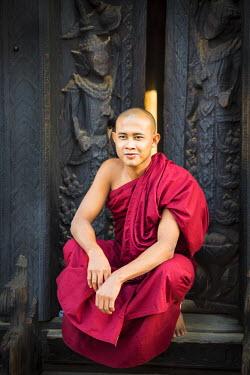 HMS2067613 Myanmar (Burma), Mandalay Division, Innwa, Bagaya Kyaung, Burmese monk sitting in front of teak wooden door