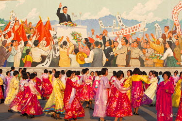 NKO0207 North Korea, Pyongyang. Students engaging in a mass dance in front of a mosaic of Kim Il Sung, depicting his triumphal return to Pyongyang in 1945. The mass dance is taking place to celebrate the Anni...