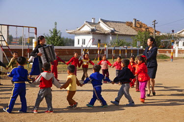 NKO0226 North Korea, Hamhung. Children playing with their teachers at the Dongbong Co-operative Farm kindergarten.