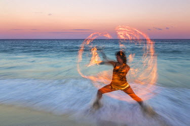 MEX1542AW Traditional mayan fire dancer at sunset on the beach. Playa del Carmen, Mexico (MR)
