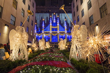 USA10677AW Christmas Angels and sparkling snowflakes at Rockefeller Center Channel Gardens with Saks department store�s Christmas light show in the background, Manhattan, New York, USA