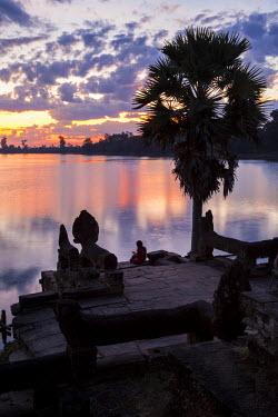 AS40CCE0036 Cambodia, Srah Srang, Royal Bath at Sunset. Visitor Checking Mobile Phone.