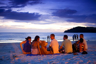 AS23MWR0026 A group of backpackers sit on a Cenang beach in Langkawi, Malaysia for the sunset. (MR)