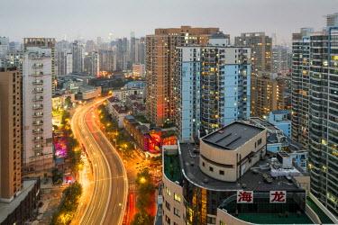 AS07PSO0388 China, Shanghai, Traffic lights blur along highway past apartment towers along Huangpu River near Nanpo Bridge at dusk on autumn evening
