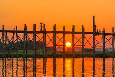 AS06IHO0818 Myanmar. Mandalay. Amarapura. U Bein Bridge. Tourists walking on the bridge at sunset.